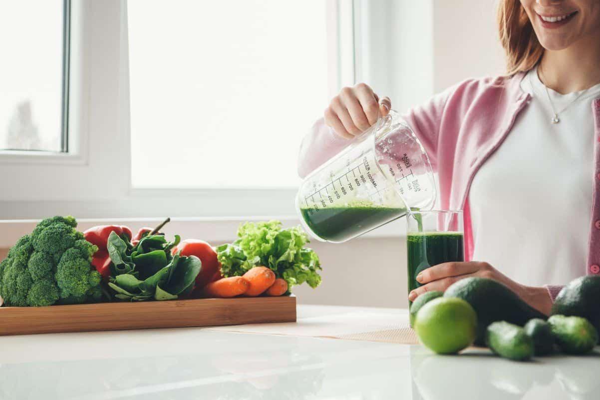 ragazza che ha appena finito di centrifugare le verdure ottenendo un succo limpido e gustoso