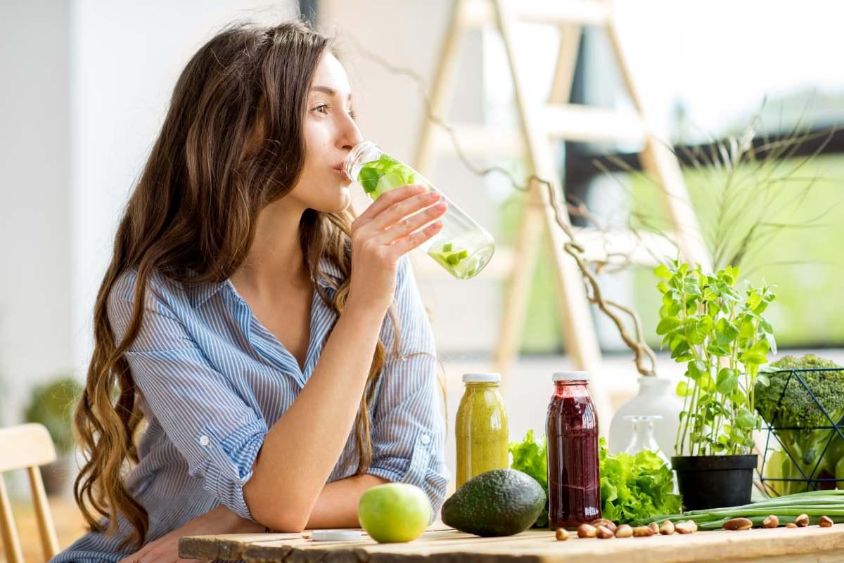 donna che beve il suo centrifugato di verdure