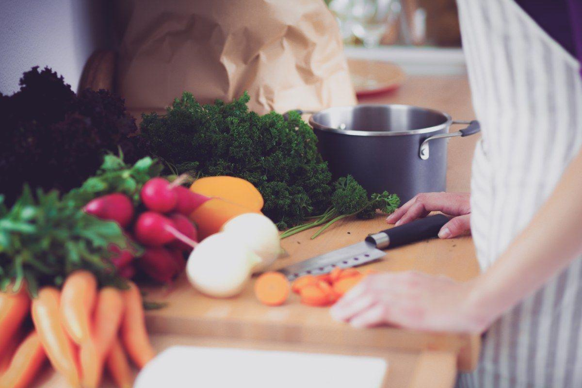 Persona taglia e affetta la frutta e la verdura e utilizza gli scarti dell'estratto appena fatto per realizzare un dolce o una ricetta sfiziosa
