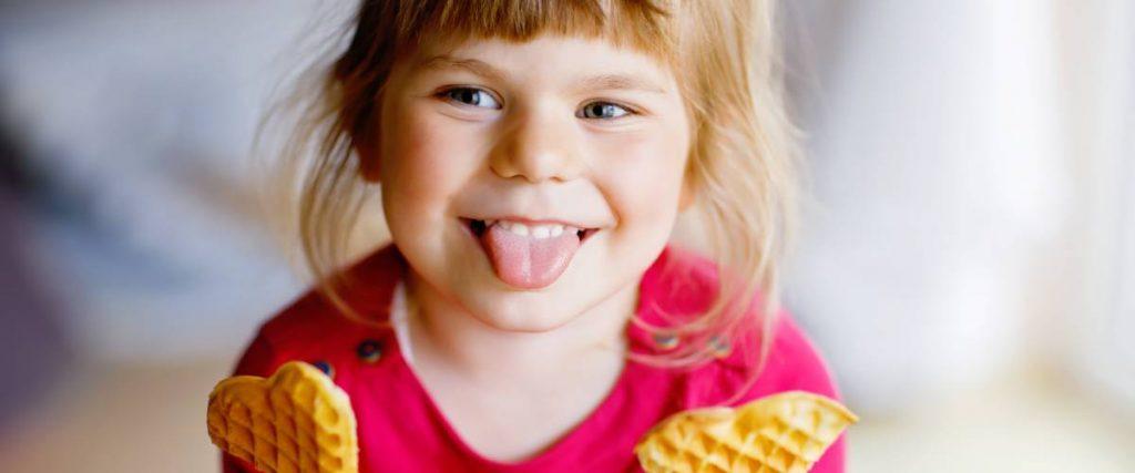 una bambina mangia il suo dolce zuccherato