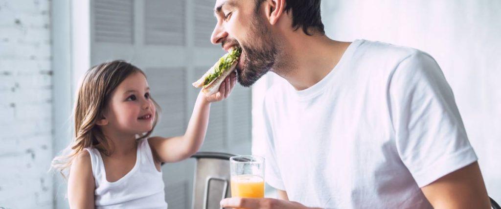 papà mangiare e beve un estratto a pranzo con la sua bambina
