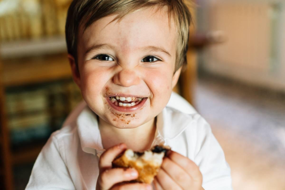 bambino mangia il suo dolce pieno di zuccheri raffinati